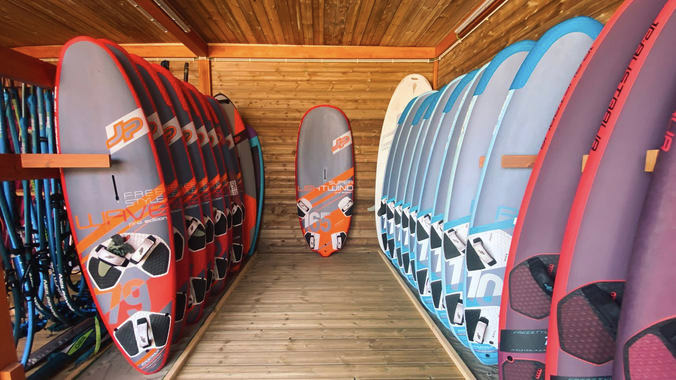 Interior em madeira do FeelViana Water Center, com pranchas de windsurf e kitesurf topo de gama